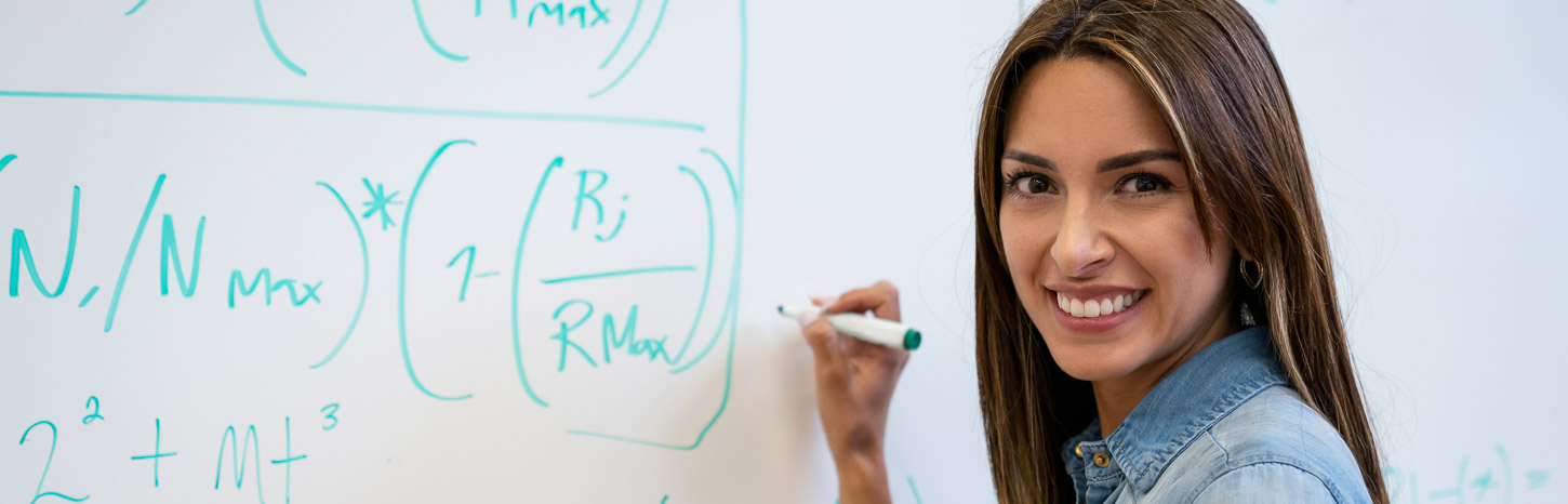 A woman writes mathematical formulas on a whiteboard while looking over her shoulder and smiling at the camera.